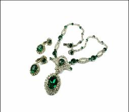Circling the necklace are hand set stones featuring emerald green faceted glass stones