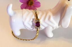 Glam, golden bracelet holds a purple amethyst glass stone