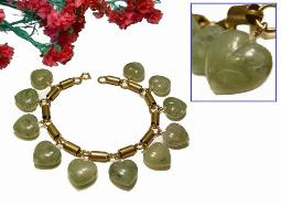Bracelet with thick carved green hearts suspending from wrist