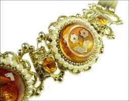 holds thLarge thick glass stones with cut flowers surrounded by faux pearls book link bracelet
