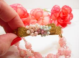 Golden intricate bow, ivy vines with wired-on pinks and blue glass beads