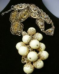 3-D articulated antique necklace jewelry, ornate golden chain suspends a large mass of light golden-yellowish balls
