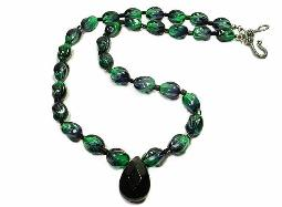 Black facet glass teardrop pendant, suspended from a line of green glass beads