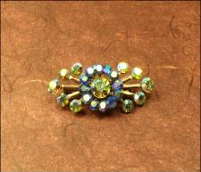 Vintage goldtone brooch has a large ab stone in the center