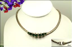 A vintage snake chain necklace with center emerald and crystal stones