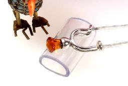 Silver brooch with orange cut glass at end